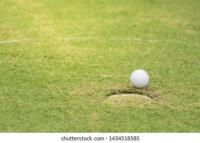 Golf ball on the lawn in the hole green golf pro player putting golf ball into hole , hand , flag in hole and Golf car