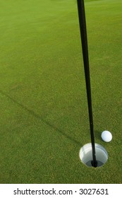golf ball on lip of cup on green as background