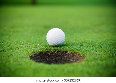 golf ball on lip of cup.  Golf ball and hole