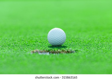 golf ball on lip of cup on green