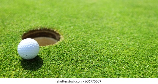 golf ball on lip of cup close up