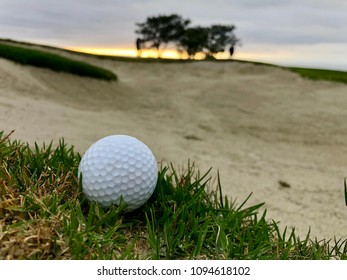 Golf ball on the lip of the sand trap