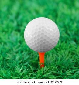 Golf ball on orange tee in golf course