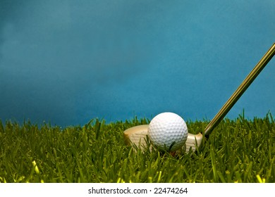 Golf ball on peg ready to be hit. Green grass with blue sky.