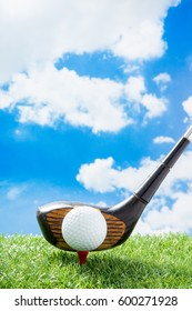 golf ball on red tee with driver against green fake grass and cloud and blue sky background