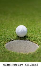 golf ball on rim golf hole