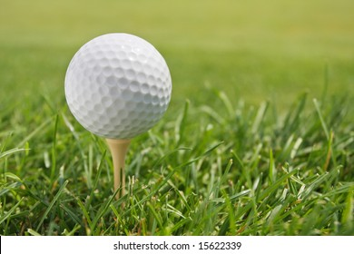 Golf Ball on Tee against grass with shallow depth of field.