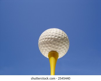 Golf ball on tee against blue sky background