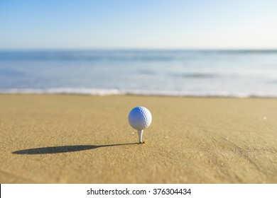 Golf Ball on a tee at a California beach with white wave with fine sand