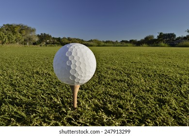 golf ball on tee on cloudless blue sky morning