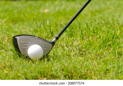Golf ball on a tee with driver and shallow depth of field focusing on the ball