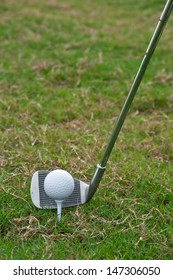 Golf ball on tee in front of driver on course