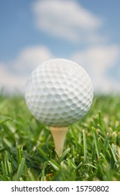 Golf Ball on Tee in front of blue sky and clouds. Vertical format.