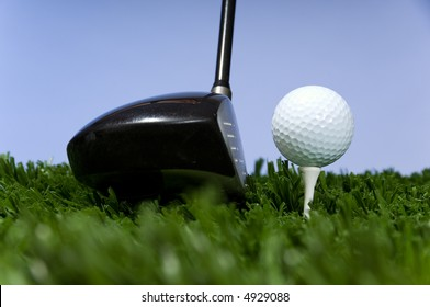 golf ball on tee on grass with blue sky with a driver