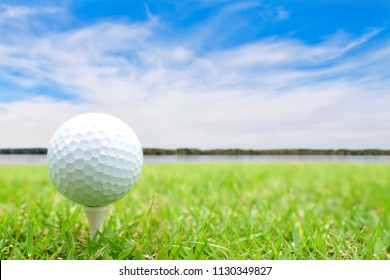 Golf ball on tee in green grass at the beautiful golf course at the ocean side on blue sky and clouds background.Ready to shot.Sport Competition Concept.