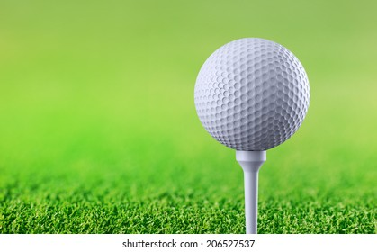 Golf ball on tee on green background