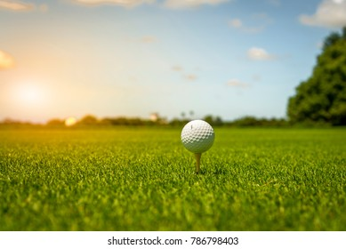 Golf ball on tee in green grass at golf course.