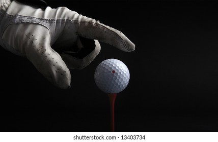 golf ball on tee with hand with glove going for the ball over black background