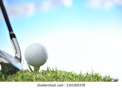 golf ball on tee with iron club head cloud sky background
