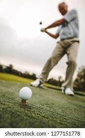Golf ball on tee with male player practising a shot at driving range. Focus on golf ball on tee with golfer taking a shot.