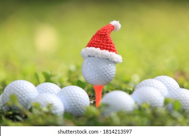 Golf ball on tee with Santa Claus' hat  for holiday season concept of golf course background