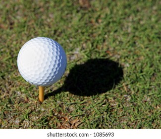 Golf ball on a tee with a shadow