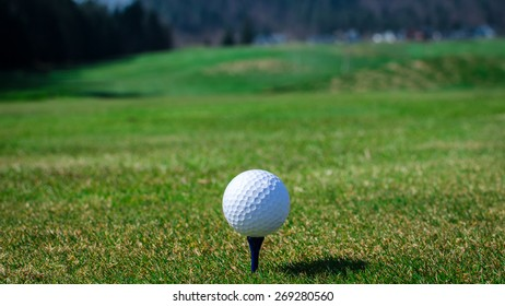 Golf ball on teeing area with green grass ahead and mountains in background. Soft focus or shallow depth of field.