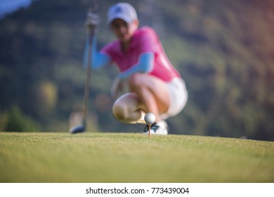 golf ball on wooden tee ready to hit by woman golf player, to checking line out of the golf ball before hit the ball to the fairway for the best result