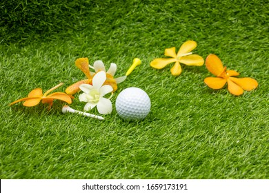 Golf ball with orchid flower and tee on green grass