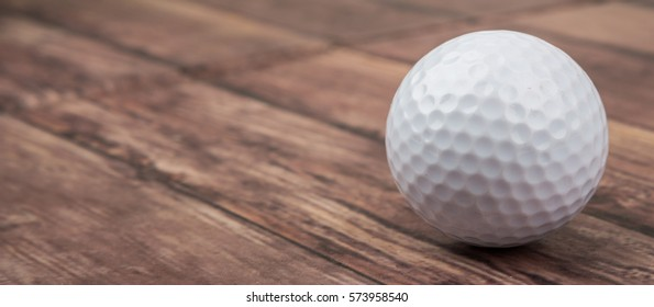 Golf ball over wooden background