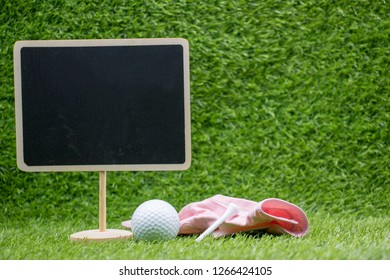 Golf ball with pink glove and black board on green