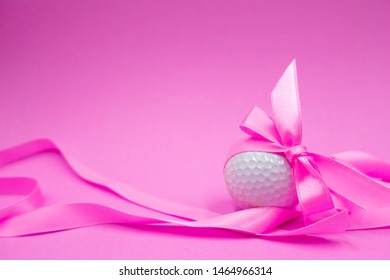 Golf ball with pink ribbon on pink background idea for lady golfer or baby shower pink party invitation.