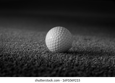 Golf ball put on grass at course with dramatic style.