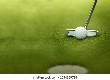 A golf ball is putted with a golf iron, golf club. Putt, Background. golf ball on green