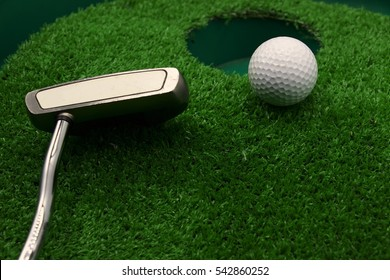 golf ball and putter near hole on green grass.