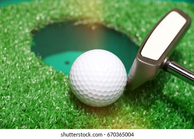 Golf ball and putter next to hole