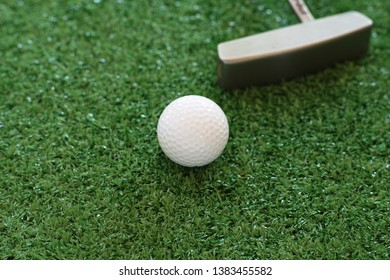 Golf ball and putter on green lawn background, copy space