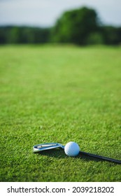 Golf ball and putter on the green grass next to the hole. Top view of the sporting event for the game of golf. Summer vacation and hobbies.