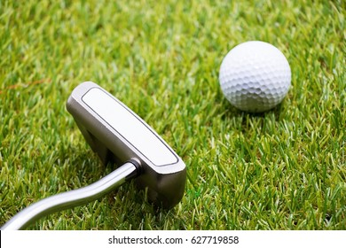 Golf ball with putter on green course