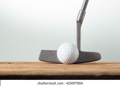 golf ball and putter on old wood