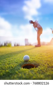 Golf ball putting by woman golf player in background, golf ball spining to the hold on the green of golf course with early light of sunset