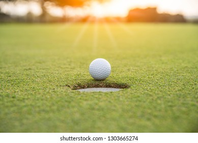 Golf ball putting on green grass near hole golf to win in game at golf course with blur background and sunlight ray