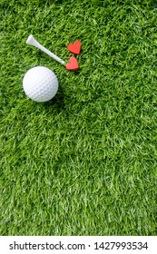 Golf ball with red heart on green grass
