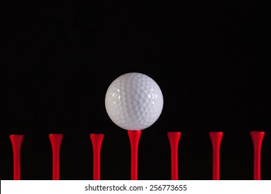 Golf ball and red tee on a black background