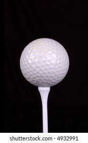 A golf ball rests on a tee. Black background.
