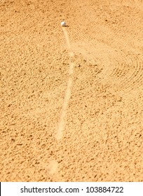 Golf ball rolling into sand trap on golf course