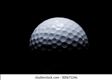 Golf ball with round dimples fading into the black background. Low key studio lighting