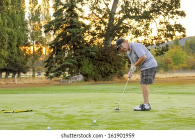 The golf ball runs slowly across the green to the cup leaving trails in the heavy dew on the autumn morning golf green as the sun rises behind the golfer's shoulder promising dryer greens soon.