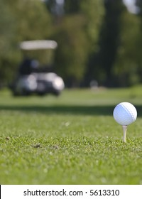 Golf ball set against green grass with cart in the background