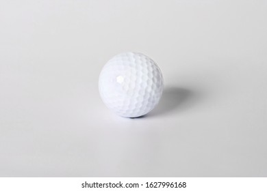 Golf ball shot in studio, white background with light,